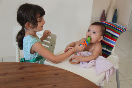 Svara is all about helping to feed Talisa!  Here Talisa is having some breastmilk icecubes inside of a mesh feeder